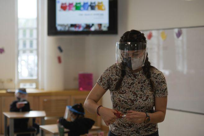 Una profesora dicta clase de manera presencial, mientras que los estudiantes que se encuentran en sus casas se ven en la pantalla del televisor en videollamada.