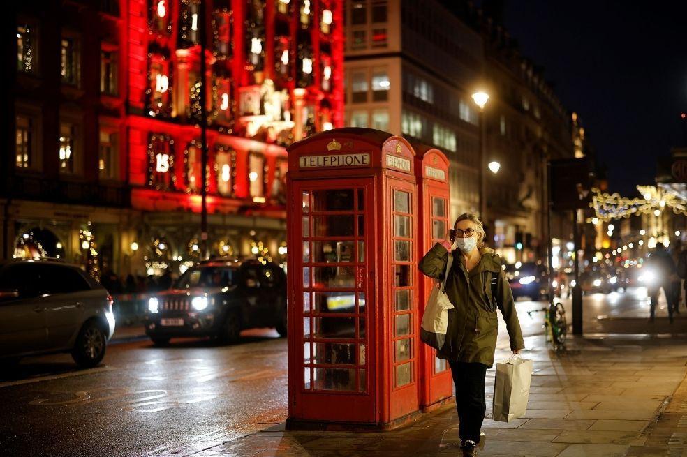 Una mujer que lleva una tapabocas pasa frente a las populares cabinas telefónicas rojas de Londres en Inglaterra.